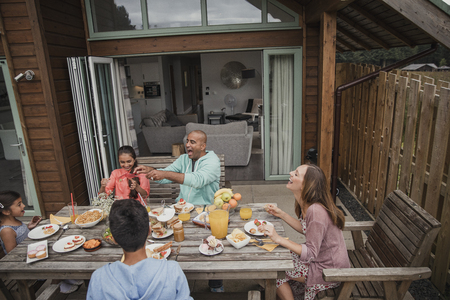 Family laughing and having fun during their brunch on vacation.