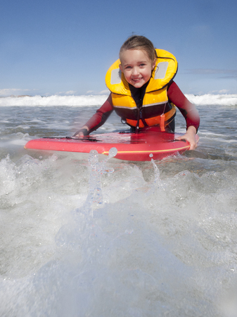 Little girl is smiling for the camera as she bodyboards in the sea with a life jacket on.