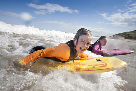 Two little girls are smiling for the camera while bodyboarding in the sea. Фото со стока - 105269726