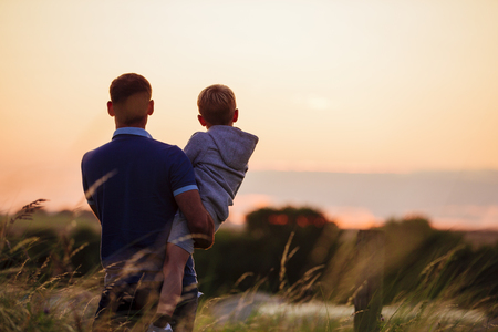Father and son watching the sun set over the beach while stood on the sand dunes.