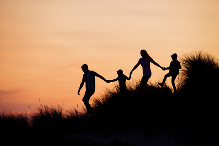 Silhouette of family running through the sand dunes at sunset.