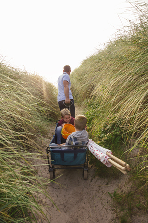 Rear view of father pulling a cart up a sand dune while his two children sit in the back.