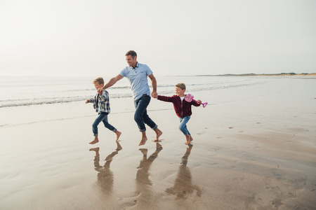 Father and two children having fun, laughing and smiling while running along the sea front.