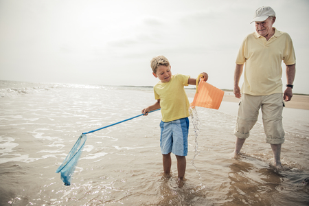 Little boy playing in the sea while his grandad stands by close. Stock Photo