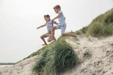 Side view of two little boys jumping over a sand dune at the beach.