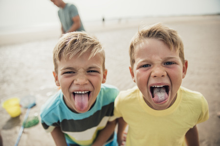 Two little boys looking at the camera being cheeky and sticking their tongues out.