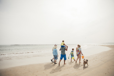 Rear view of a family walking along the beach with their dog while on holiday. 写真素材