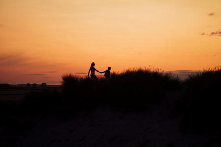 Silhouette of a mother and son walking through the sand dunes at sunset.