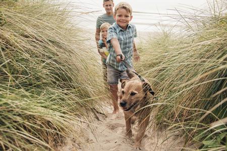 Vista de ángulo bajo de un niño y su familia paseando al perro por las dunas de arena.