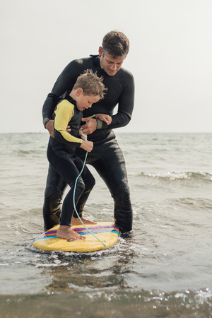 Front view of a father teaching hos son how to surf at the beach.