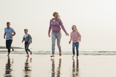 Low angle view of family running from the tide coming in at the seaside. Having fun on their beach holiday.
