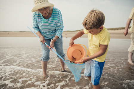 Searching for sea artifacts with a bucket and fishing rod at the beach with grandma. 写真素材