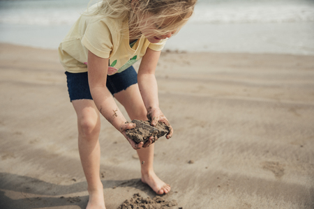 Little girl looking at rocks and getting dirty hands on the beach.