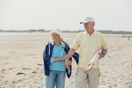 Elderly couple walking along the beach, arm in arm, on holiday.