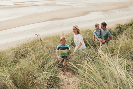 High angle view of a family walking through the sand dunes. 写真素材