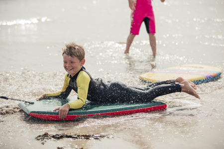 Little boy having fun at the beach, being pulled along on a body board.