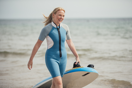 Woman is coming back from a fun surfing session at the beach. She is pulling a surf board.