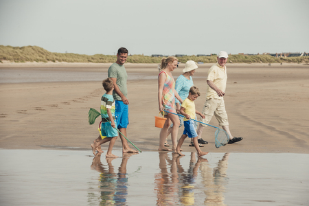 Three generations of family walking along the beach to the sea front.