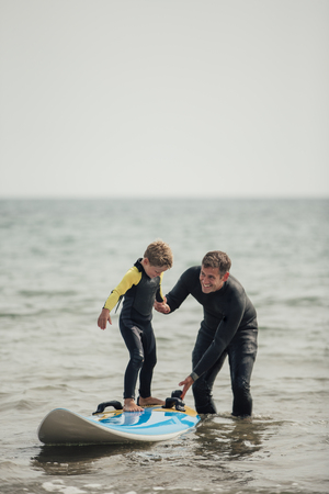 Little boy getting shown how to surf at the beach with his father.