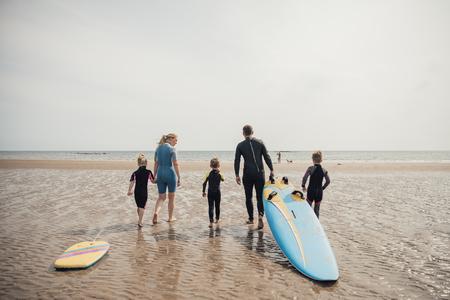サーフィンに行くために水辺まで歩く家族。