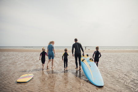 Family walking to the water's edge to go surfing.