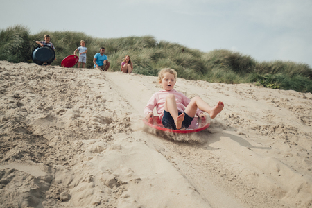 Little girl having fun, sliding down a sand dune while her family wait at the top.