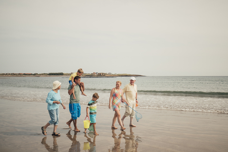 Three generation family walking along the seafront while on a beach holiday. Stock Photo