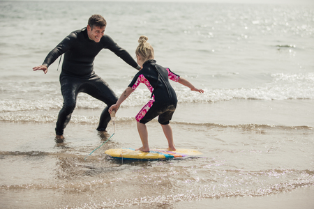 Mid adult male teaching a little girl how to surf at the beach.