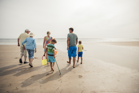 Rear view of a family walking down to the waters edge while on holiday.
