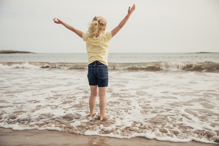 Little girl being free at the beach with her hands up in the air.