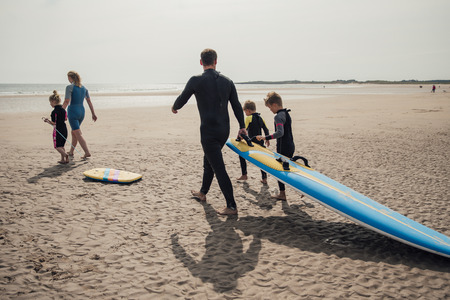 Rear view shot of a family walking down to the seaside to go surfing.