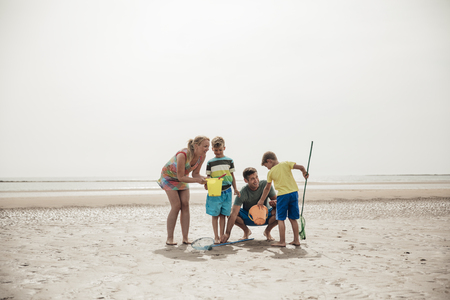 Wide angle view of a family stood on a beach looking through buckets for sealife and shells. Banco de Imagens