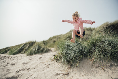 Little girl jumping over a sand dune while on holiday with her family, having some fun.