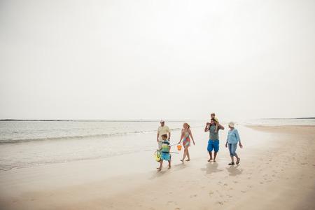 ビーチ沿いを歩く家族の広角図。