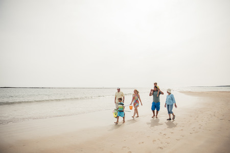 Wide angle view of a family walking along the beach.