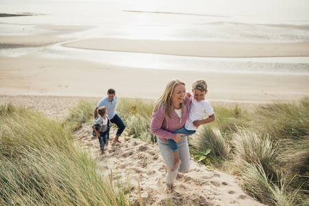 High angle view of a family walking up the sand dune from the beach. Foto de archivo - 97863096
