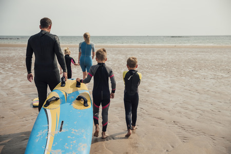 Rear view of a family walking to the waters edge to learn how to surf.