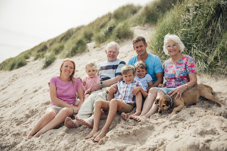 Family getting their photo taken as they sit all together on a sand dune. Stock Photo