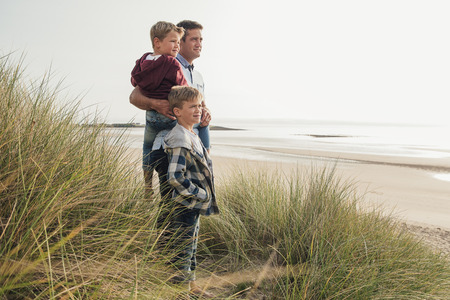 Single parent and his two sons looking at the beautiful view at the beach. Stock Photo