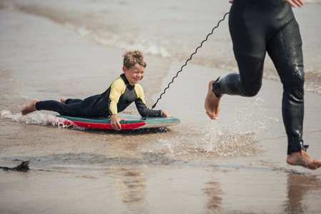 Little boy being pulled along by his father at the beach on a bodyboard.