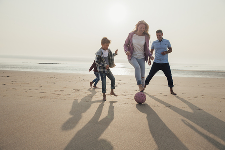 Mother showing off her football tricks while playing football at the beach with her family. Banco de Imagens