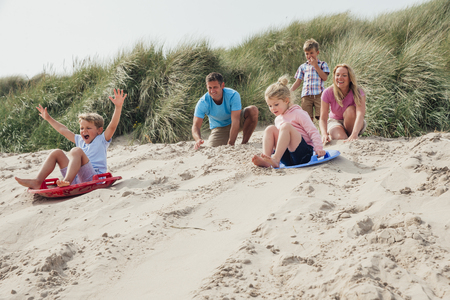 Siblings racing down the sand dunes. On holiday, relaxing at the beach. Family waiting at the top of the dunes.