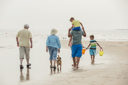 Rear view of a family walking to the sea front while on holiday at the seaside. 写真素材