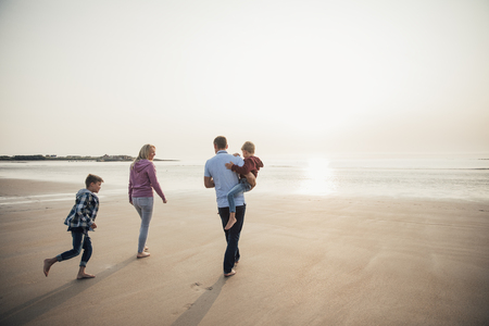 Rear View of family with two children walking down to the waters edge while on holiday.
