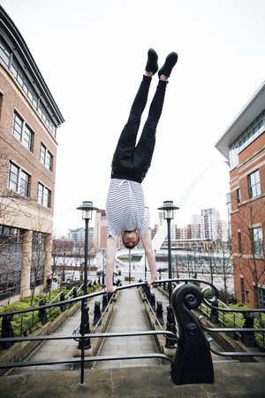 Teenage freerunner is doing a handstand on bridge railings in the city.