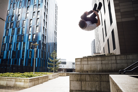 Freerunner macht einen Flip von einer Mauer in der Stadt.