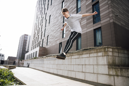 Young freerunner is jumping down from a wall in the city.