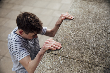 Freerunner is suspended from the side of a building, gripping on with his hands.