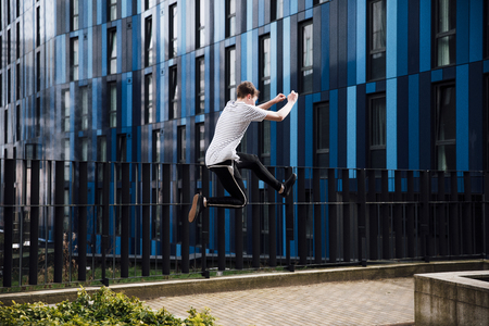 Freerunner is jumping between walls in the city.