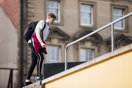 Freerunner is making his way up the side of a building to start a parkour session in the city.